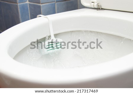 Flow of water inside a toilet with deodorant - stock photo