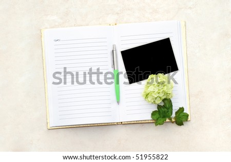 Flower and blank photo with pen on an open note book. - stock photo