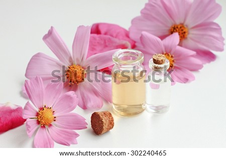 flower aroma oil liquid in glass vials fresh organic cosmetics aromatic natural white empty space beauty care setting - stock photo