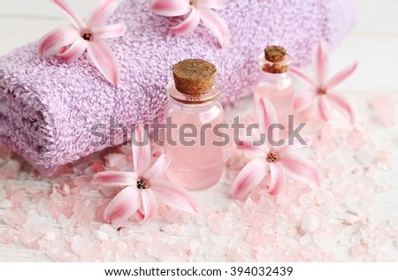 Flower aromatherapy. Bottles with essential oils, pink hyacinth flowers, sea bath salt. Soft light and focus - stock photo