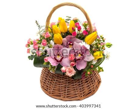 Flower arrangement in a wicker basket . Bright spring flowers - stock photo