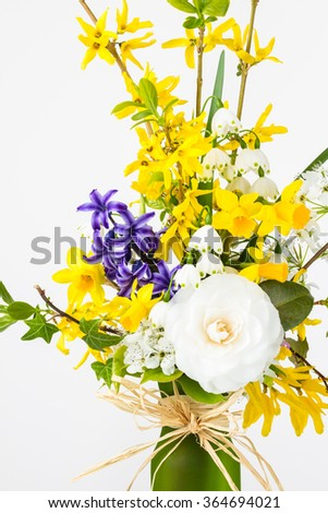 Flower arrangement of spring blooms:  forsythia, daffodils, snowdrops, narcissus, camellia, and ivy. - stock photo