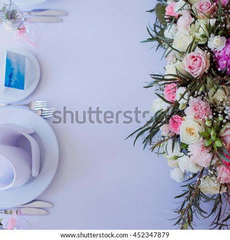 Flower arrangement on the table. Flowers and white tablecloth, wedding, roses, peonies. Top view, place for text. - stock photo
