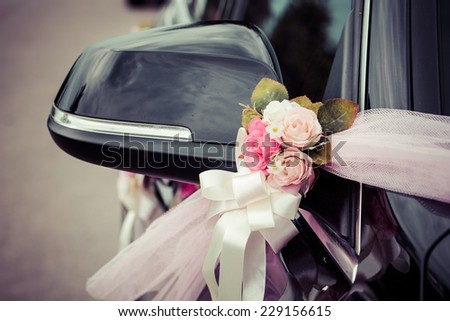 Flower arrangement tied to a wedding car, process color - stock photo