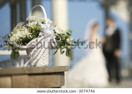 Flower basket with Caucasian bride and groom blurred in background.