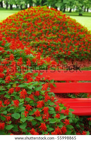 flower bed and red bench in garden - stock photo