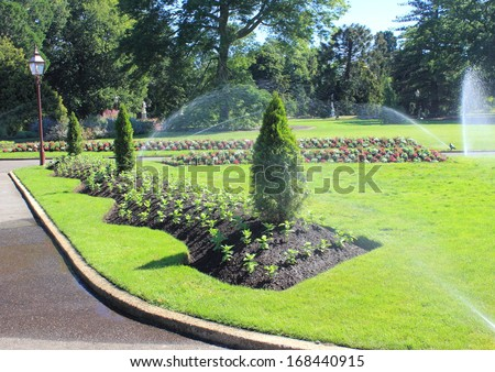 Flower beds being watered by sprinklers in Australian botanical gardens - stock photo
