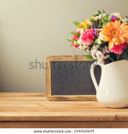 Flower bouquet and chalkboard on wooden table - stock photo