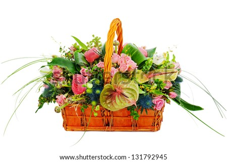 Flower bouquet arrangement centerpiece in a wicker gift basket isolated on white background. - stock photo