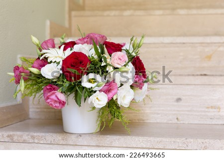 Flower bouquet in a white vase on the marble stairs