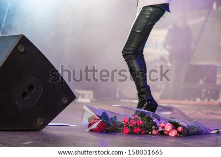 Flower bouquets lay at the feet of singer during performance - stock photo