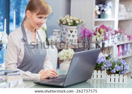 Flower business in action. Small business entrepreneur florist managing her business working by her laptop - stock photo