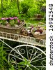 Flower cart with two baskets in summer garden - stock photo