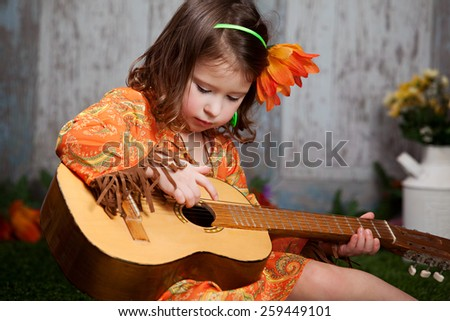 Flower Child.  Adorable preschooler dressed in retro 60's clothing, sitting on the grass, playing a guitar.   - stock photo