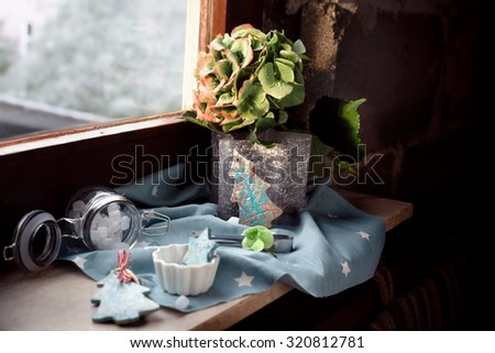 Flower Christmas: xmas decorations, candles and sweets set on old house window sill. Natural light, shallow focus on the flowers and the tree decoration near it. Lightly toned photo. - stock photo