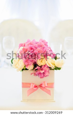Flower composition for an event party or wedding reception is on the white table