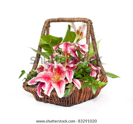Flower composition with lilies in basket - stock photo