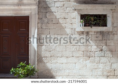flower decorated door and window on stone facade - stock photo