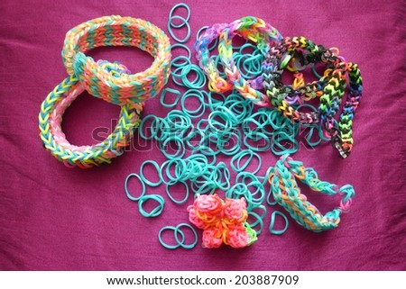 Flower design loom band bracelets in different colors and loose turquoise loom bands - stock photo
