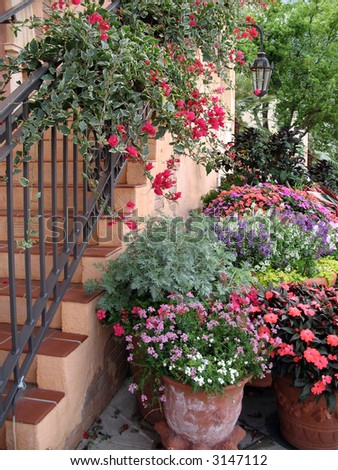 flower-draped staircase and flower pots - stock photo