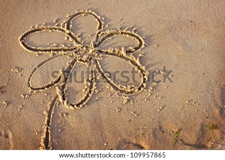 Flower drawn in the sand/Sea background with a sand/simple flower drawing in the sand on the beach - stock photo