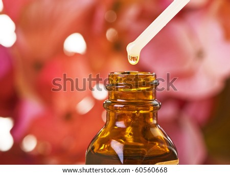 Flower essence in amber bottle with blossoms. Shallow depth of field - stock photo
