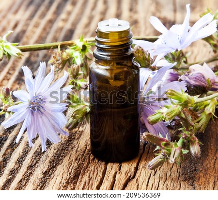 Flower Essential Oil Bottle on Wooden Table - stock photo