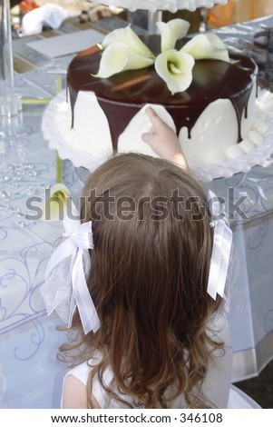 Flower girl sneaking a tate of the ganache covered wedding cake. - stock photo