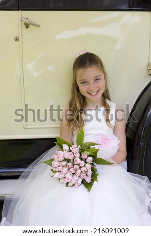Flower girl (10-12) with bouquet of flowers sitting by vintage car, smiling, portrait, elevated view