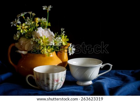Flower in a yellow tea pot and vintage cup of coffee,cozy home rustic decor, cottage living, still life image dark tone - stock photo