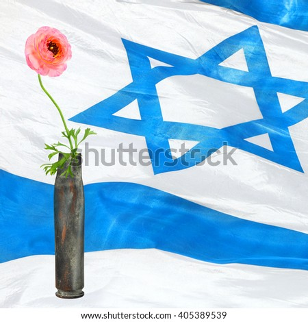 Flower in the cartridge case with flattering Israeli national flag in blur background. Revival - stock photo
