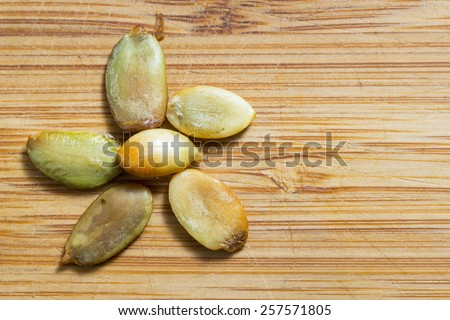 Flower. Kernels of a pumpkin seeds  on a bamboo board. - stock photo