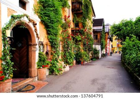 Flower lined street in the traditional Austrian village of Hallstatt - stock photo