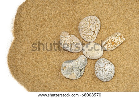 flower made with stones on a sand background - stock photo
