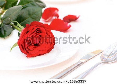 Flower of love. Close up of lying on the table rose near the plate and fork.