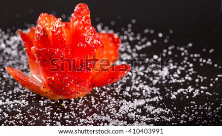 Flower ornament from ripe strawberry on a black plate. Close up, horizontal shot, small depth of sharpness - stock photo