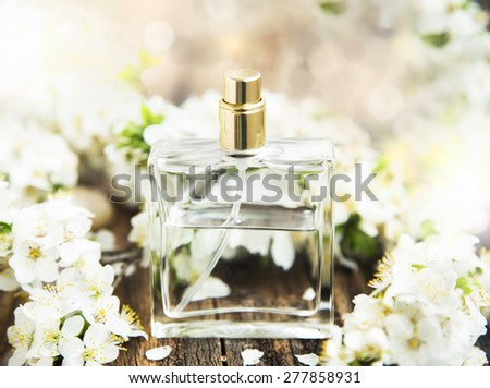 Flower Perfume in Transparent Bottle with Spring Blossom - stock photo