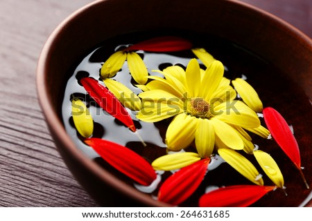 Flower petals in bowl, close-up, on wooden table background - stock photo