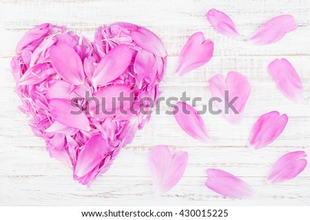 Flower petals of peonies in heart shape on white wooden background. Valentine background. Greeting card. Top view
