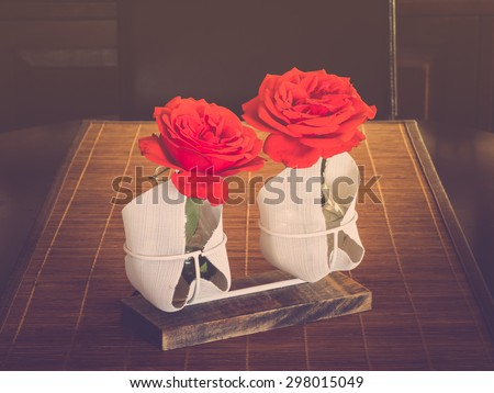 Flower piece with two red roses on table, vintage toned - stock photo