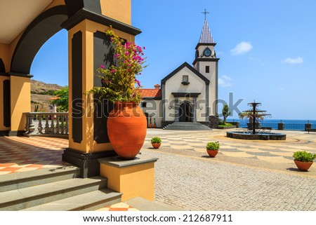 Flower pot on square with traditional Portuguese church building, Madeira island, Portugal  - stock photo