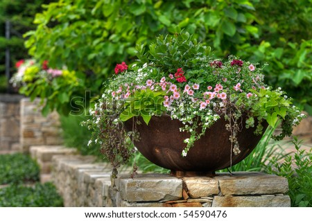Flower pot or planter with geranium, calibrachoa (million bells), sweet potato vine, framing house entrance - stock photo