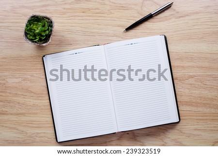Flower pot, pen, notebook lie on light brown desktop - stock photo