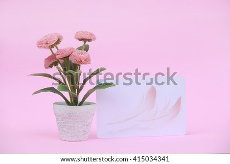 Flower pot with blank paper note on the pink background - stock photo