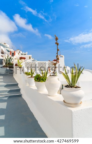 Flower pots and steps to beautiful Firostefani village with typical white architecture, Santorini island, Greece - stock photo