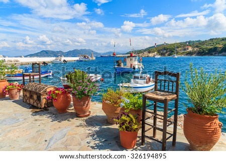 Flower pots on and view of fishing boats anchoring in Kokkari bay, Samos island, Greece