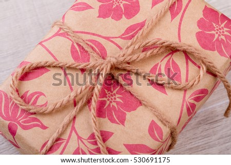 Flower print wrap and rope. Package on wooden background. Ideas of wrapping gifts. Be thankful for presents.