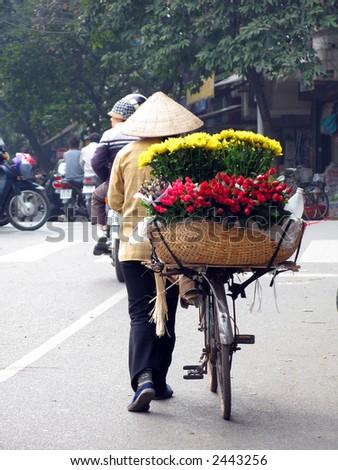 Flower seller on Bicycle in Hanoi Vietnam - stock photo