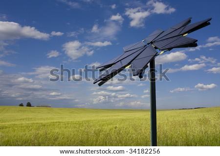 Flower shaped solar panel against rural background - stock photo