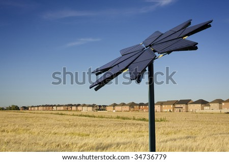 Flower shaped solar panel, farmers field and row of houses - stock photo